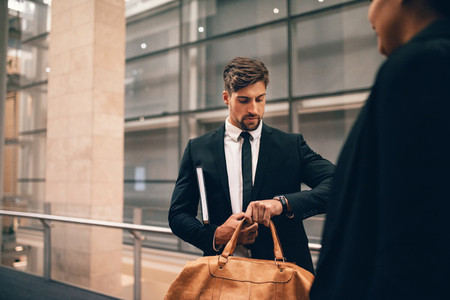 Businessman at airport with bag looking at his watch