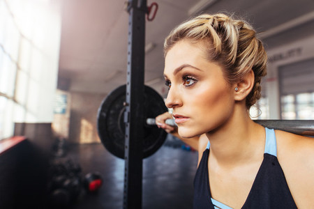 Woman working out at the gym using weight bar
