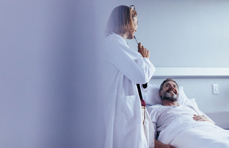 Doctor interacting with patient in hospital ward