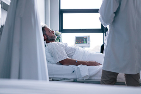 Sick man lying in hospital bed with doctor
