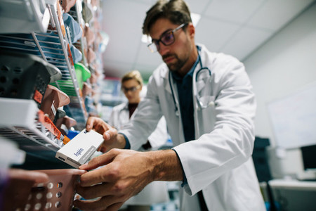 Pharmacist looking for a drug on shelf