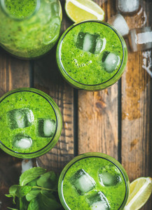 Fresh green smoothie with ice cubes in rustic wooden tray