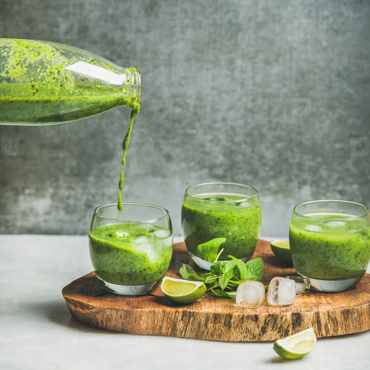 Fresh smoothie pouring from bottle with ice  mint and lime
