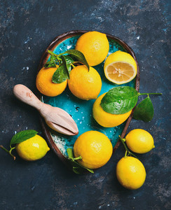 Freshly picked lemons with leaves in blue ceramic plate