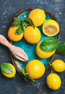 Freshly picked lemons with leaves in bright blue ceramic plate