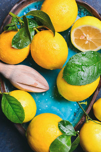 Close up of freshly picked lemons with leaves in blue plate