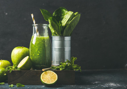 Green smoothie in glass bottle with fresh fruits  copy space