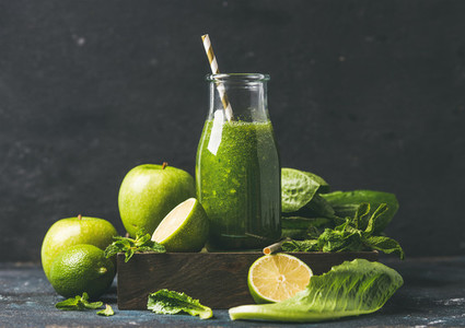 Green smoothie in glass bottle with apple romaine lettuce lime