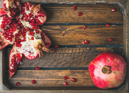 Fresh ripe pomegranates  one cut in pieces in wooden tray