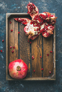Fresh ripe pomegranates cut in pieces in wooden tray