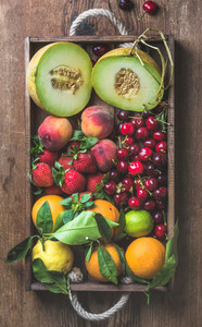 Healthy summer fruit variety  Melon  sweet cherries  peach  strawberry  orange and lemon in wooden tray over rustic background