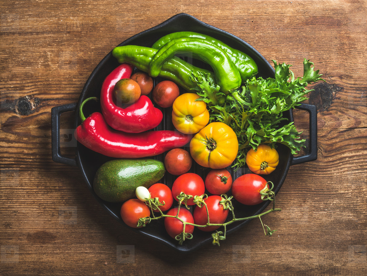Fresh raw vegetable ingredients for healthy cooking or salad making in black grilling iron pan over rustic wooden background