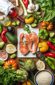 Dinner cooking ingredients  Raw uncooked salmon with vegetables  rice  herbs  lemon  artichokes  spices and bottle of rose wine on white ceramic board over rustic wooden background  top view