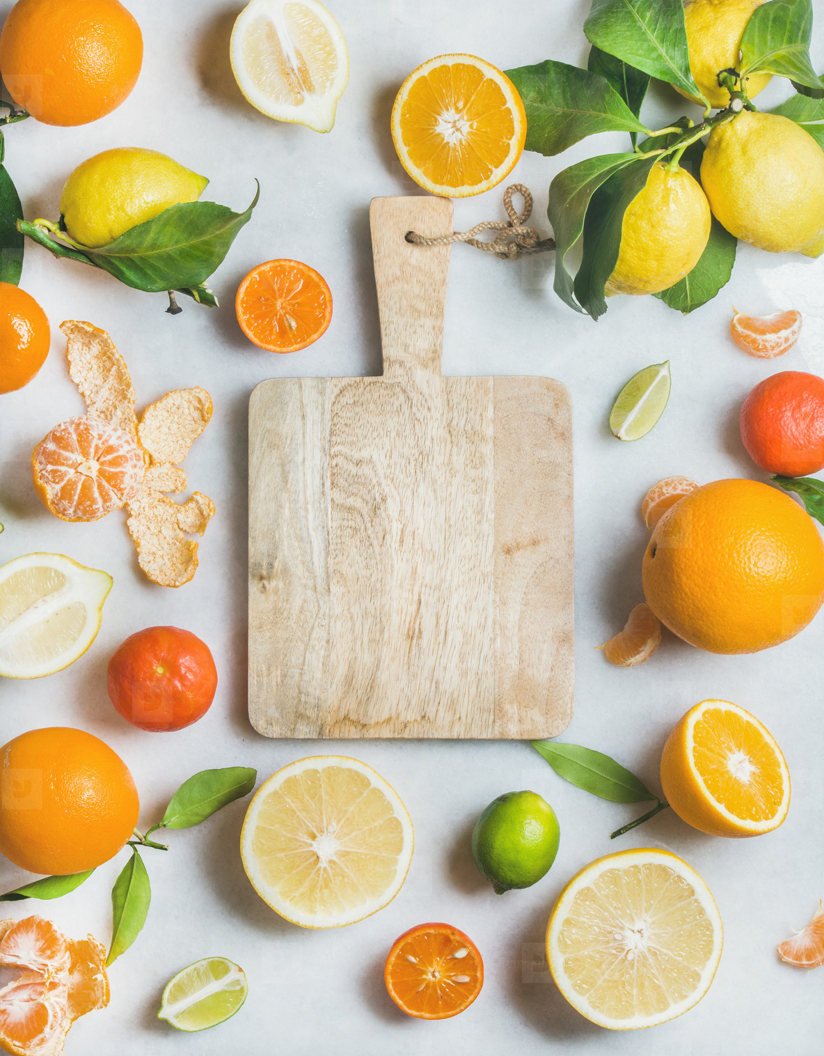 Variety of fresh citrus fruit and wooden board in center