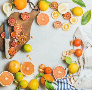Citrus fruits slices over grey marble background  top view