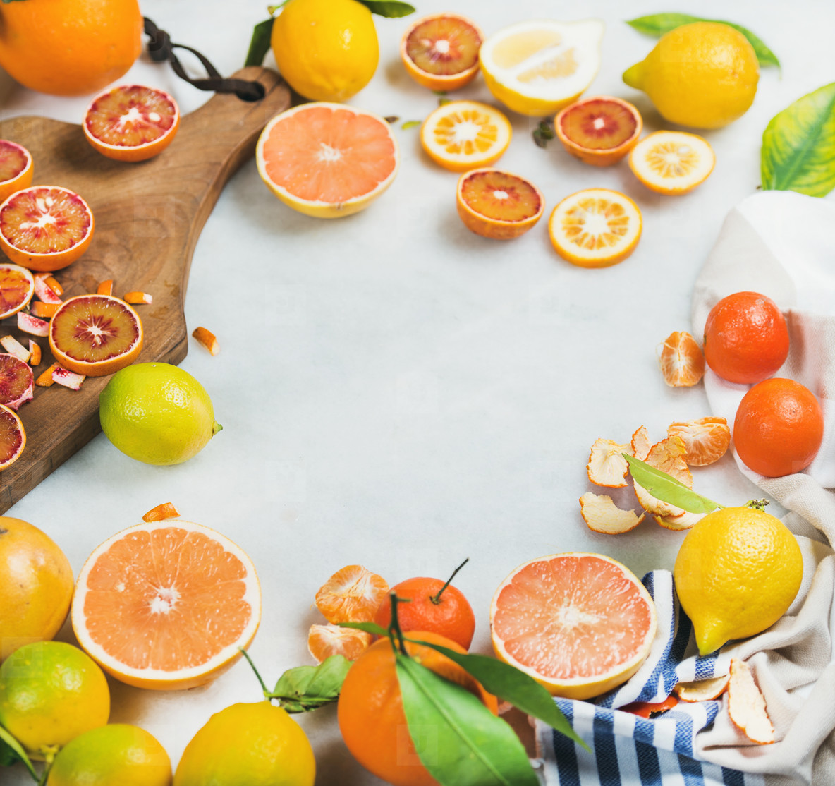 Citrus fruits slices on wooden board over grey marble background
