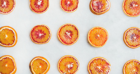 Fresh juicy blood orange slices over light marble table background