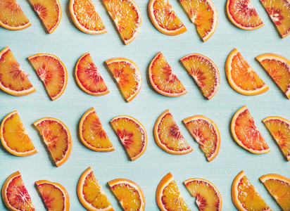 Fresh juicy blood orange slices over blue painted table background
