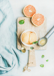 Pink grapefruit sorbet with fresh mint leaves on wooden board