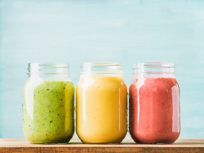 Fresh blended fruit smoothies of various colors and tastes in glass jars  Green  yellow  red