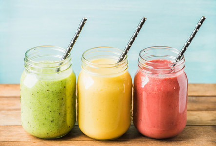 Three jars of fresh fruit smoothies with various colors and tastes  Green  yellow  red