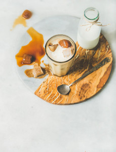 Iced caramel latte coffee cocktail with milk in glass