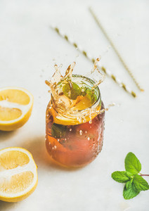 Summer cold Iced tea with lemon and herbs  vertical composition