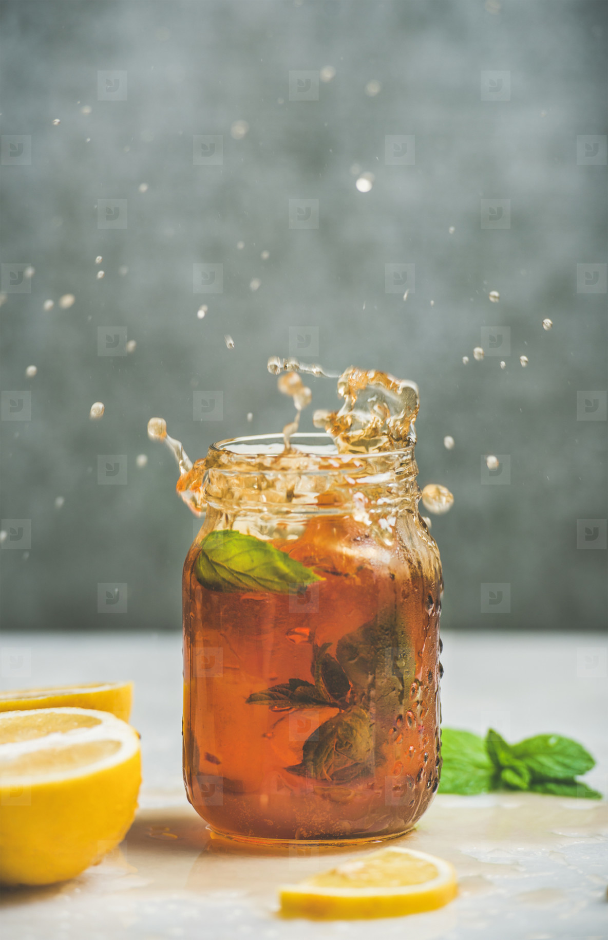 Iced tea with bergamot  lemon  mint in jar with splashes
