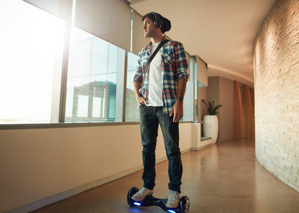 Young man on a hover board in office corridor