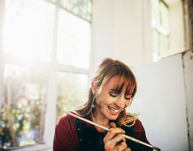 Female artist smiling with paint brush in studio