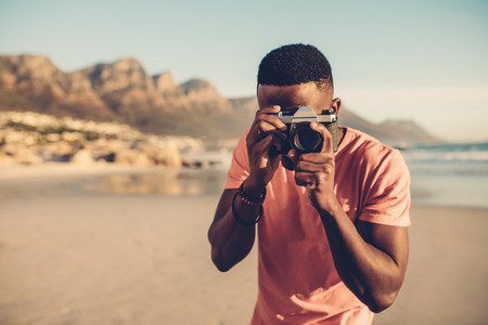 Black guy using digital camera on beach