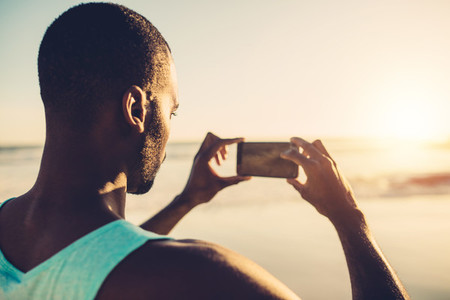 African man doing mobile photography on the beach