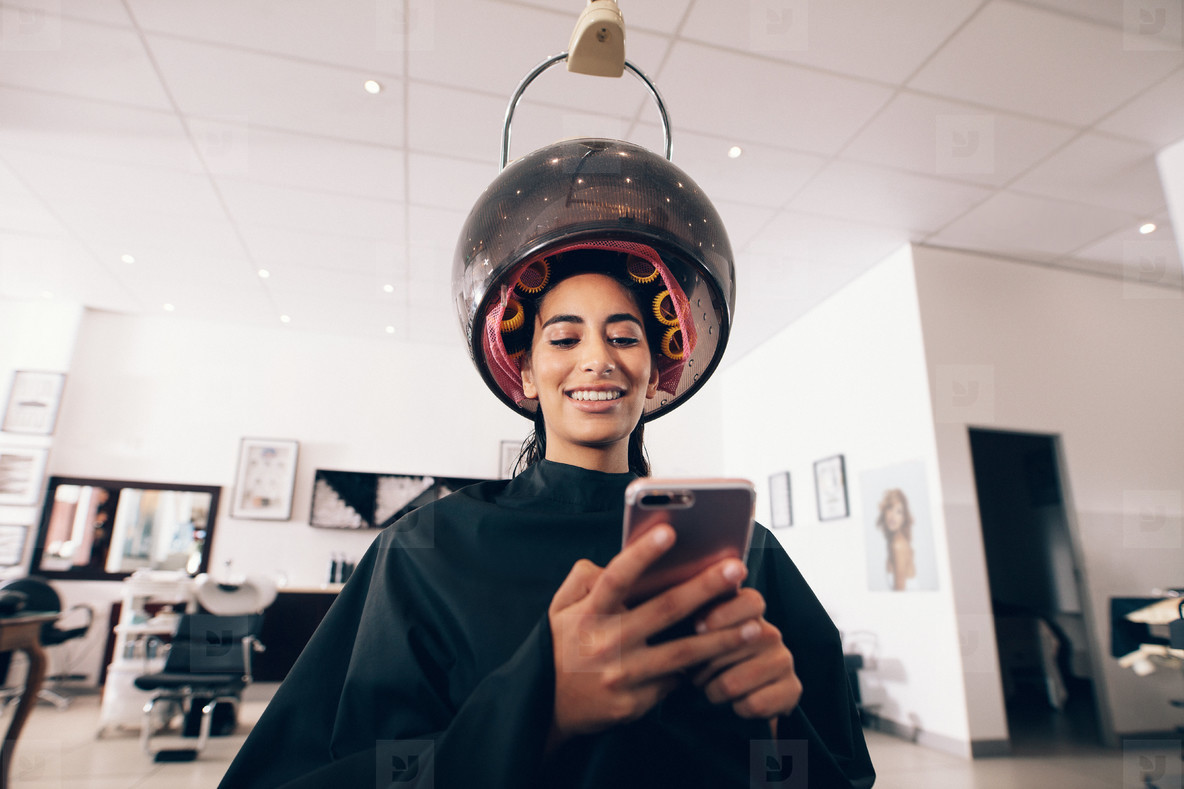 Woman using mobile phone at the beauty spa