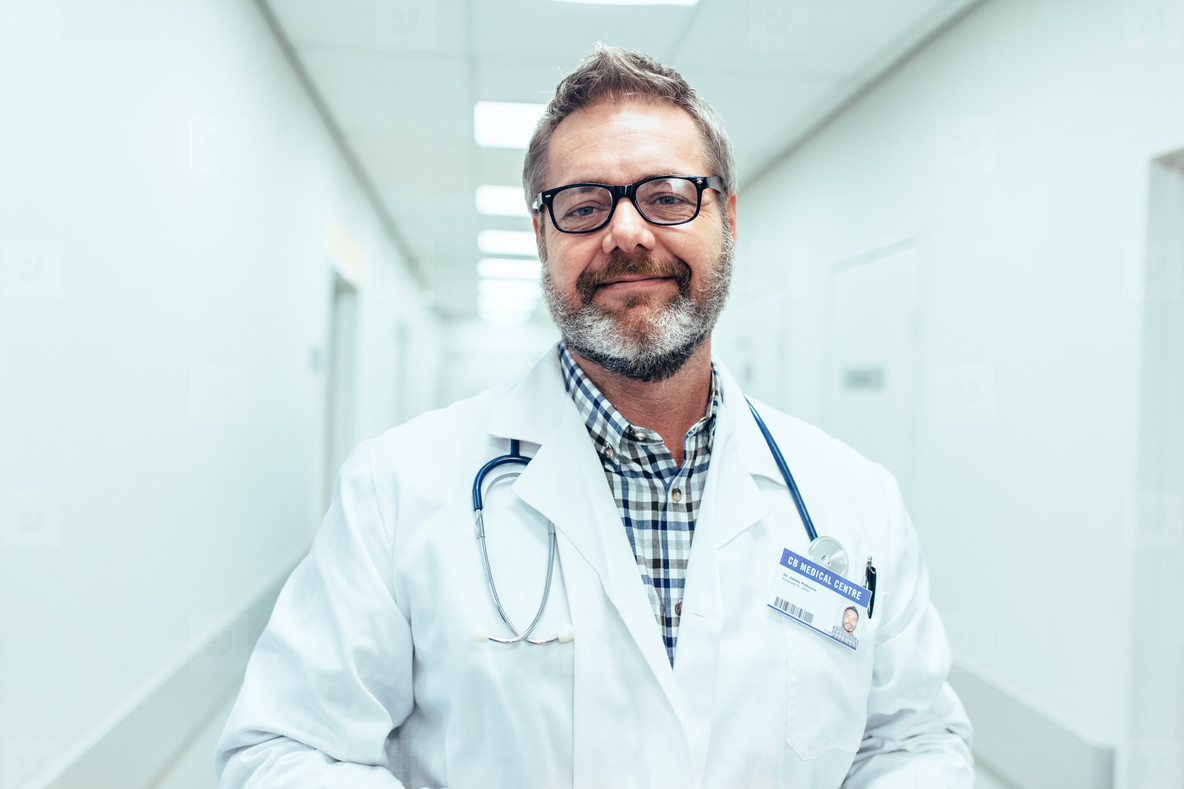 Happy mature male doctor standing in hospital corridor