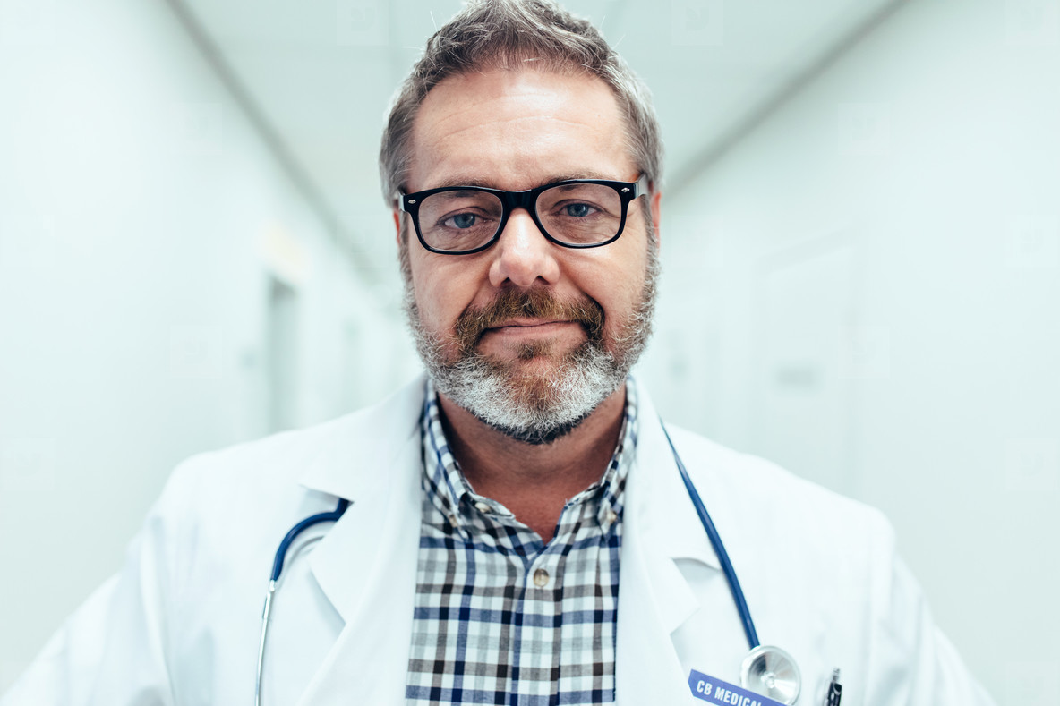 Mature male medical doctor standing in hospital