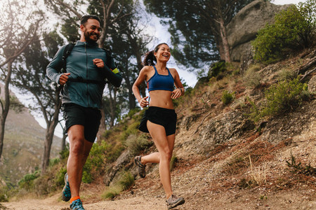 Healthy young couple running on mountain trail