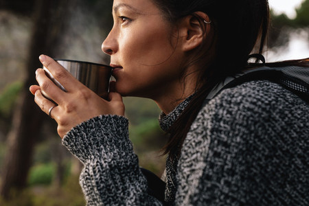 Young asian female hiker drinking coffee