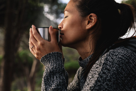 Young asian woman having coffee outdoors