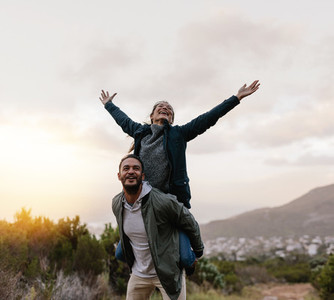 Young man piggybacking his girlfriend in countryside
