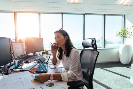 Businesswoman speaking over phone in office