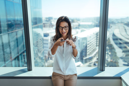 Businesswoman sending voice message using mobile phone