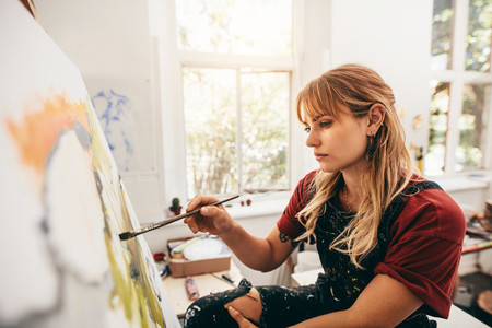 Creative female artist drawing picture in her studio