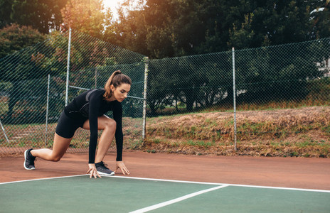 Beautiful female exercising on tennis court