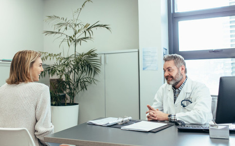 Happy medical doctor talking with woman in clinic