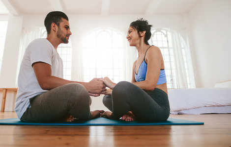 Couple sitting together on the yoga mat holding hands