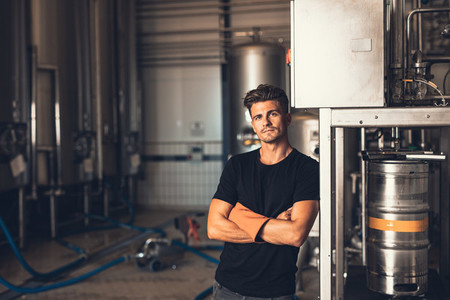 Young man standing by beer filling machine