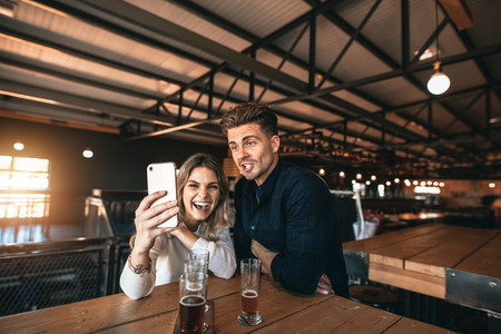 Couple taking selfie on mobile phone inside the bar