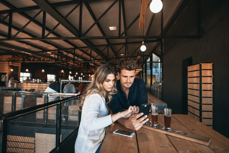 Couple at the bar using mobile phone