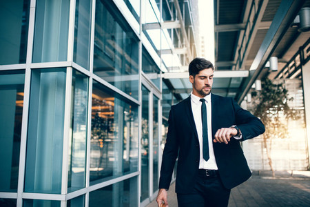 Young businessman looking at his watch while walking at airport