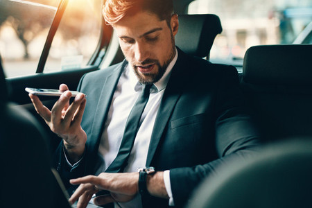 Businessman travelling by car using smart phone and checking tim